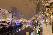 Ljubljanica river with snowy banks and streets, illuminated by christmas lights.