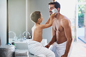 Cropped shot of a handsome young man teaching his son how to shave in the bathroom