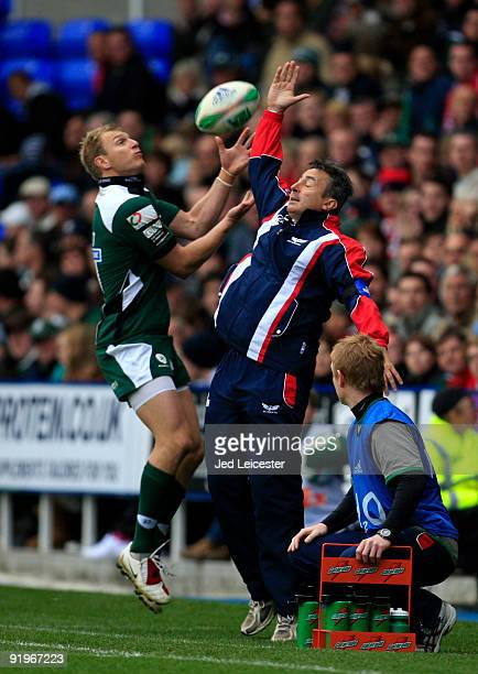 Llanelli coach Nigel Davies jumps up to catch the ball on the touchline with London Irish full back Peter Hewat during the Heineken Cup match at the...