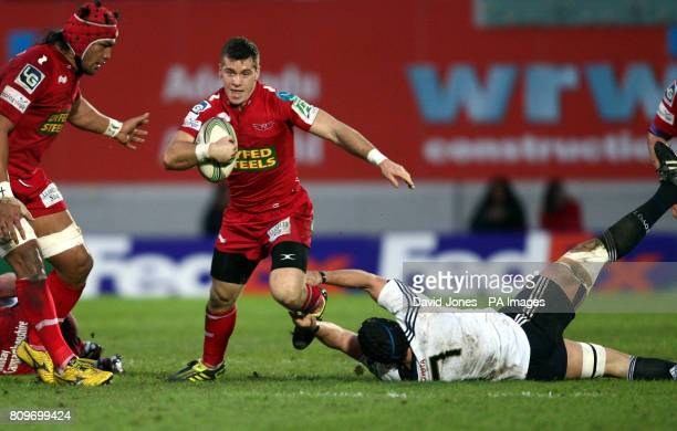 Llanelli Scarlets' Gareth Davies breaks away from Munster's Niall Ronan during the Heineken Cup match at Parc y Scarlets Llanelli