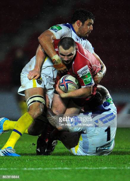 Llanelli Scarlets' Ken Owens is tackled by ASM Clermont Auvergne's Damien Chouly and Thomas Domingo during the Heineken Cup Pool Four match at Parc y...