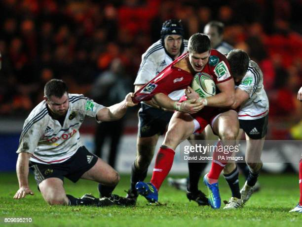 Llanelli Scarlets' Scott Williams is held by Munster's Damien Varley and Ronan O'Gara during the Heineken Cup match at Parc y Scarlets Llanelli