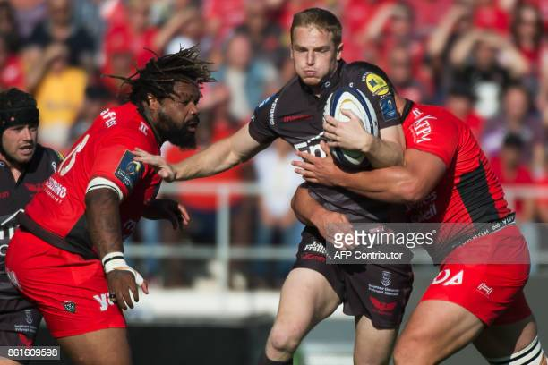Llanelli's Wales wing Johnny McNicholl vies with RC Toulon's French centre Mathieu Bastareaud during the Champions Cup rugby union match between RC...