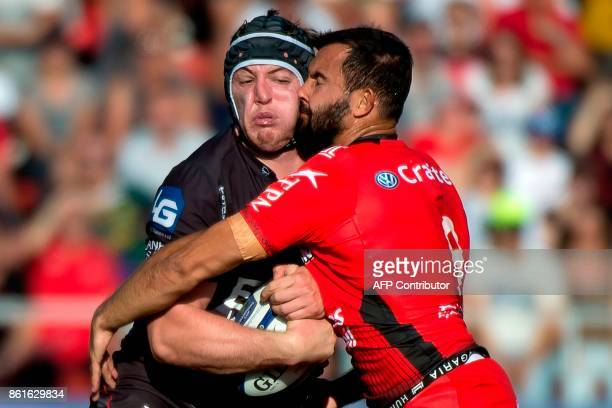 TOPSHOT Llanelli's Welsh prop Alun Wyn Jones vies with RC Toulon's French scrumhalf Eric Escande during the European Champions Cup rugby union match...