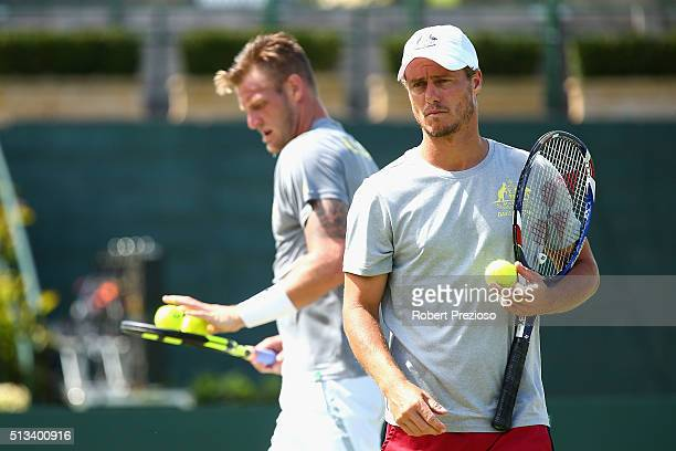 Llewton Hewitt captain of Australia looks on as Sam Groth of Australia prepares to serve during a practice session after the official draw ahead of...