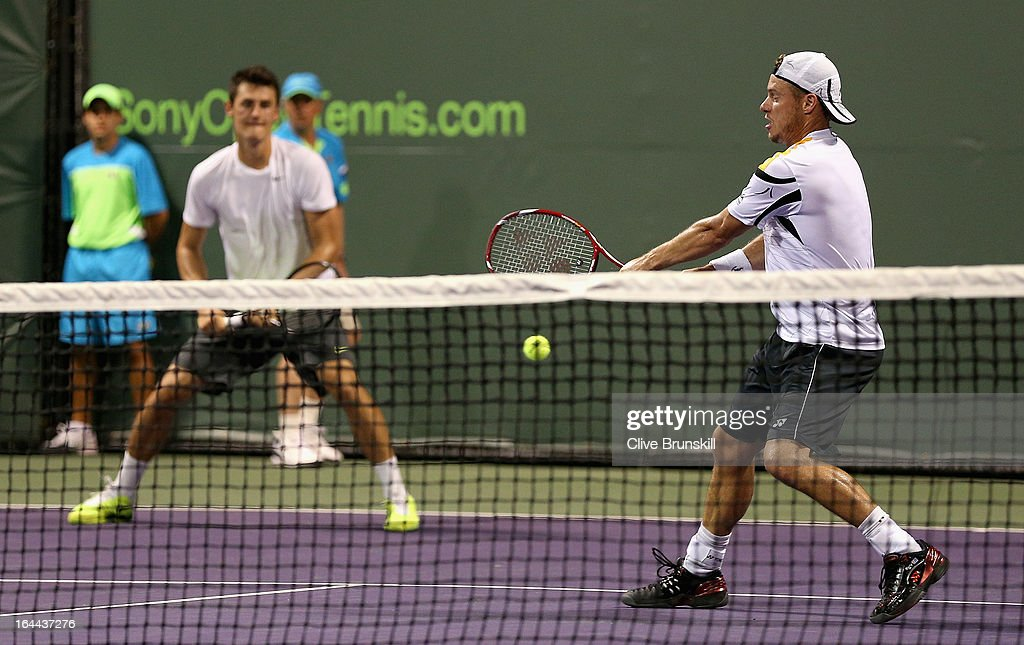 Lleyton Hewitt and Bernard Tomic of Australia in action against Ivan Dodig of Croatia and Marcelo Melo of Brazil during their first round doubles match at the Sony Open at Crandon Park Tennis Center on March 23, 2013 in Key Biscayne, Florida.