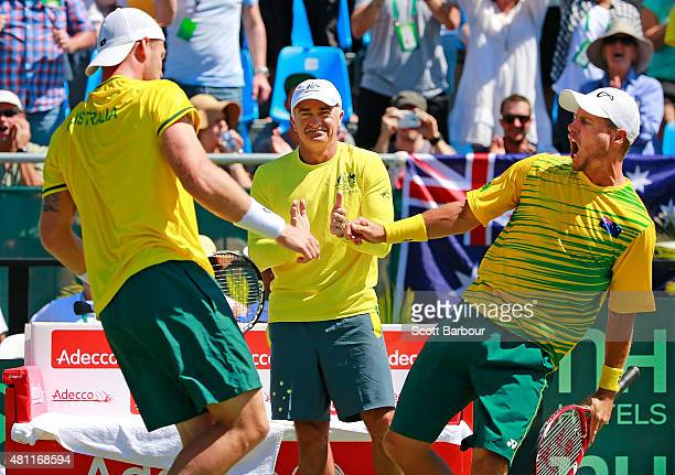 Lleyton Hewitt and Sam Groth of Australia bump chests as they celebrate winning a game while Wally Masur captain of Australia looks on as Sam Groth...