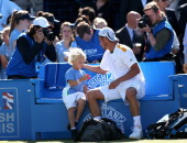 Lleyton Hewitt of Australia celebrates victory with his son Cruz after the Men's Singles quarter final round match against Juan Martin del Potro of...