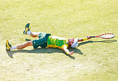 Lleyton Hewitt of Australia falls to the ground as he celebrates winning the reverse singles match between Lleyton Hewitt of Australia and Aleksandr...