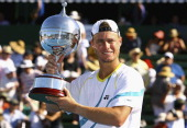 Lleyton Hewitt of Australia holds aloft the winners trophy after winning his match against Gael Monfils of France during day four of the AAMI Classic...