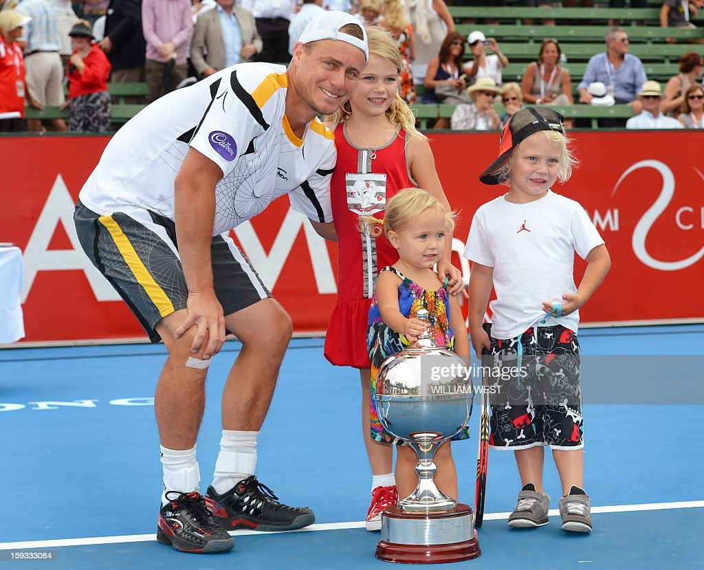 Lleyton Hewitt of Australia (L) poses with the trophy and his children Mia, (2nd L), Ava (2nd R) and Cruz (R) after defeating Juan Martin Del Potro of Argentina in the final of the Kooyong Classic in Melbourne on January 12, 2013. AFP PHOTO/William WEST IMAGE