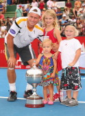 Lleyton Hewitt of Australia poses with the winners trophy and his children Ava Hewitt Cruz Hewitt and Mia Hewitt after winning his match against Juan...