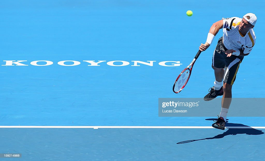 Lleyton Hewitt of Australia serves during his match against Tomas Berdych of Czech Republic during day two of the AAMI Classic at Kooyong on January...