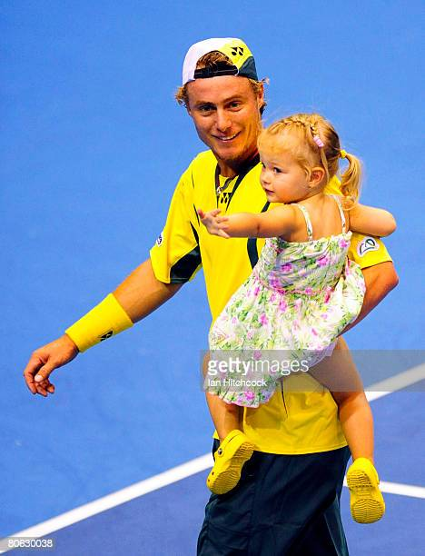 Lleyton Hewitt of Australia walks off the court with daughter Mia after winning his singles match against Kirati Siributwong of Thailand during day...