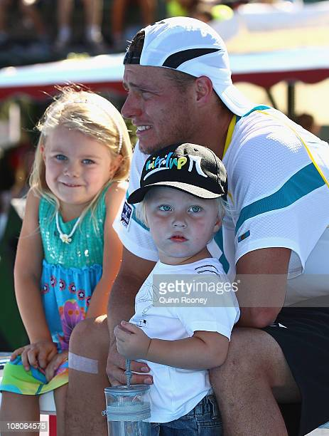 Lleyton Hewitt of Australia watches the trophy presentation with his kids Mia and Cruz after his match against Gael Monfils of France during day four...