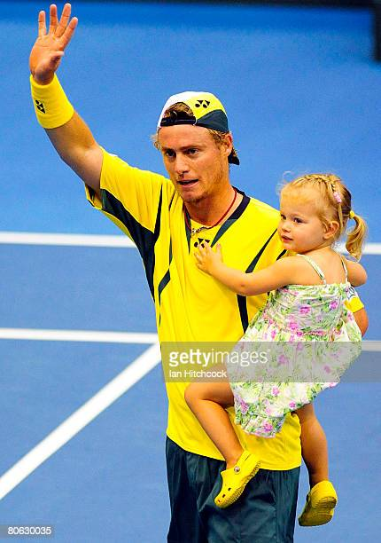 Lleyton Hewitt of Australia waves to the crowd with his daughter Mia after he won his singles match against Kirati Siributwong of Thailand during day...
