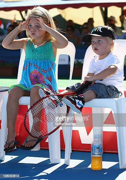 Lleyton Hewitt of Australia's kids Mia and Cruz watch their dad except the trophy after his match against Gael Monfils of France during day four of...