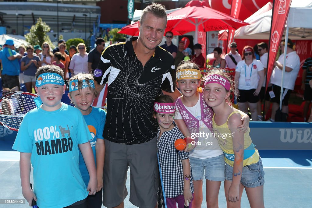 Lleyton Hewitt poses for photographs with kids from tennis hot shots on day two of the Brisbane International at Pat Rafter Arena on December 31, 2012 in Brisbane, Australia.