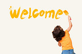 Cute little girl writing 'Welcome' with painting brush on wall background
