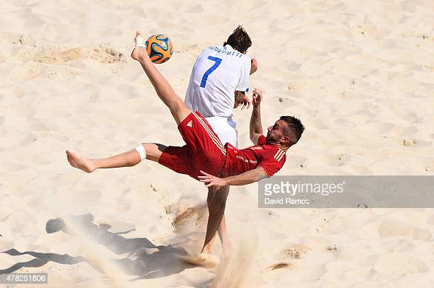 Llorenc Gomez of Spain makes a spectacular attempt on goal as Dario Ramacciotti of Italy tries to block during the Men's Beach Soccer Group B match...