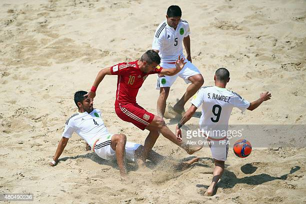 Llorenc of Spain is challenged by Francisco Cati Adrian Gonzalez and Saul Ramirez of Mexico during the FIFA Beach Soccer World Cup Portugal 2015...