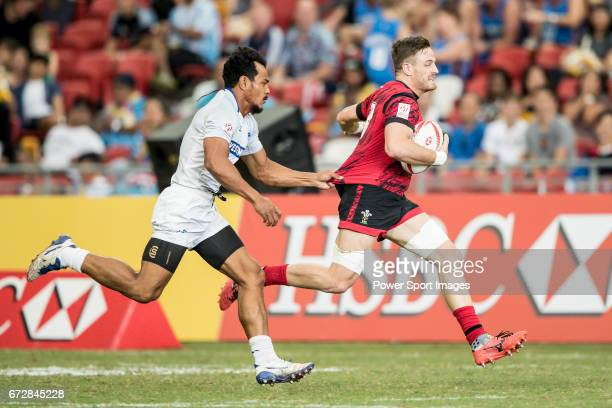Lloyd Evens of Wales runs with the ball while Tila Mealoi of Samoa is in pursuit during the match Wales vs Samoa Day 2 of the HSBC Singapore Rugby...