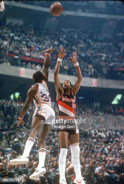 Lloyd Neal of the Portland Trail Blazers shoots over George McGinnis of the Philadelphia 76ers during an NBA basketball game circa 1978 at The...