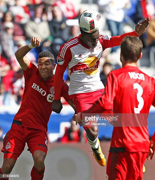 Lloyd Sam of New York Red Bulls heads the ball in front of Damien Perquis of Toronto FC during their match at Red Bull Arena on March 6 2016 in...