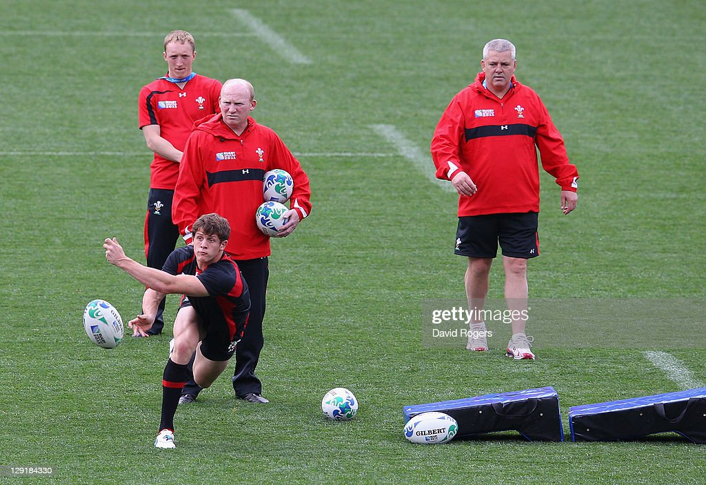 Lloyd Williams of Wales passes the ball watched by (L-R) John Ashby, Wales assistant coach Rob Howley and Wales head coach Warren Gatland during a Wales IRB Rugby World Cup 2011 captain's run at Eden Park on October 14, 2011 in Auckland, New Zealand.
