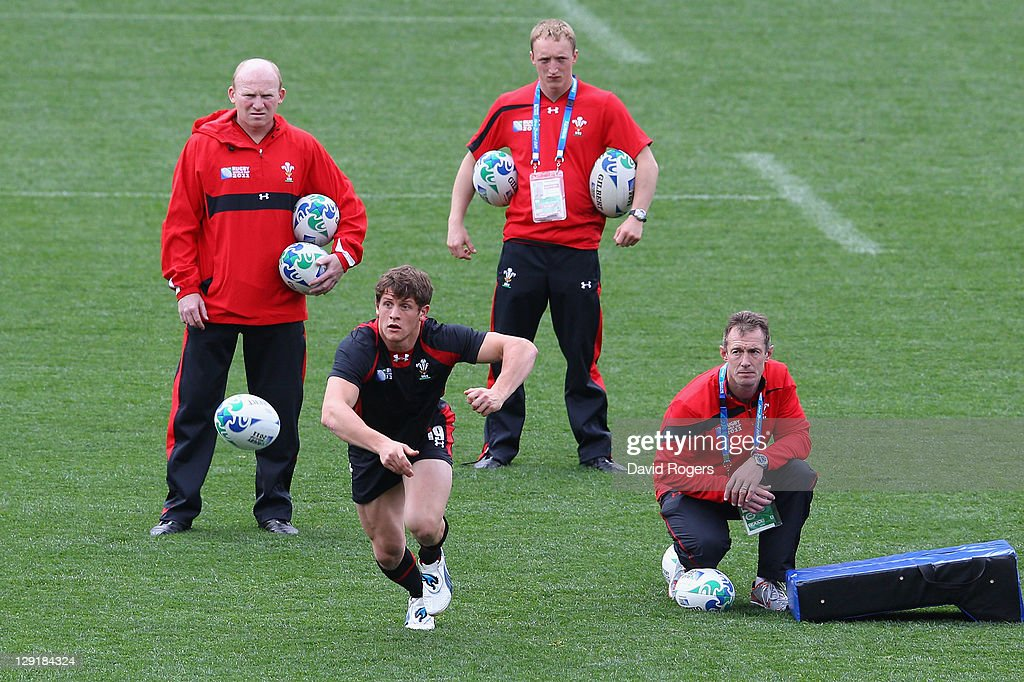 Lloyd Williams of Wales passes the ball watched by (L-R) <a gi-track='captionPersonalityLinkClicked' href=/galleries/search?phrase=Neil+Jenkins&family=editorial&specificpeople=217587 ng-click='$event.stopPropagation()'>Neil Jenkins</a> the Wales skill coach, John Ashby and Wales assistant coach <a gi-track='captionPersonalityLinkClicked' href=/galleries/search?phrase=Rob+Howley&family=editorial&specificpeople=215419 ng-click='$event.stopPropagation()'>Rob Howley</a> during a Wales IRB Rugby World Cup 2011 captain's run at Eden Park on October 14, 2011 in Auckland, New Zealand.