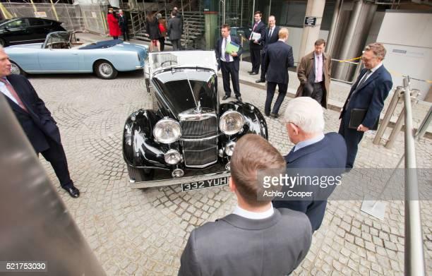 Lloyds of London staff admire a 4.3 litre Alvis reproduction car outside Lloyds of London, UK.