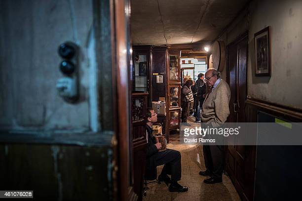 Lluis Castello owner of Musical Emporium helps a customer during his last day open to the public on January 5 2015 in Barcelona Spain Musical...