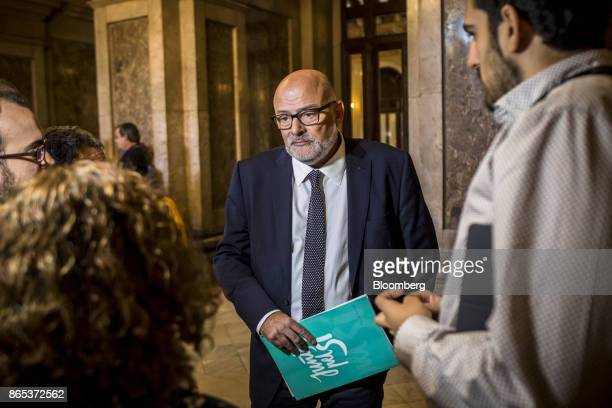 Lluis Corominas spokesman of Junts Pel Si or 'Together for Yes' party holds a document following a meeting inside the Generalitat regional government...