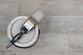 Looking down on loaded paintbrush placed across an open can of grey paint stood on a shabby style wood floor