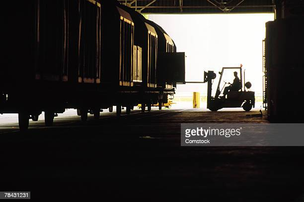 Loading cargo onto train with forklift