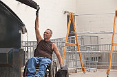 Loading dock worker with spinal cord injury in a wheelchair putting a bag in the dumpster