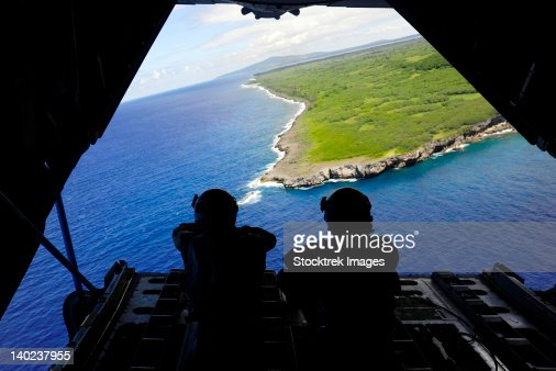 Loadmasters look out over Tumon Bay from a C-130 Hercules. : Stock Photo