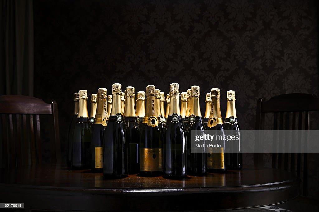 loads of champange bottles on living room  table