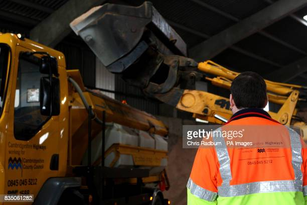 A JCB loads salt grit onto a gritting lorry at Whittlesford Depot in Cambridgeshire