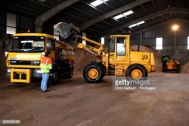 A JCB loads salt grit onto a gritting lorry at Wittlesford Depot in Cambridgeshire