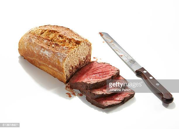Loaf of bread cut into slices of raw beef