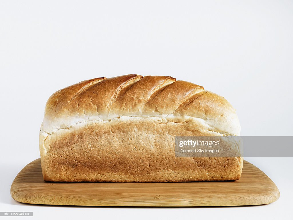 Loaf of bread on chopping board, close-up : Stock Photo