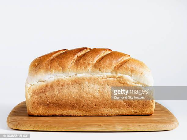 Loaf of bread on chopping board, close-up