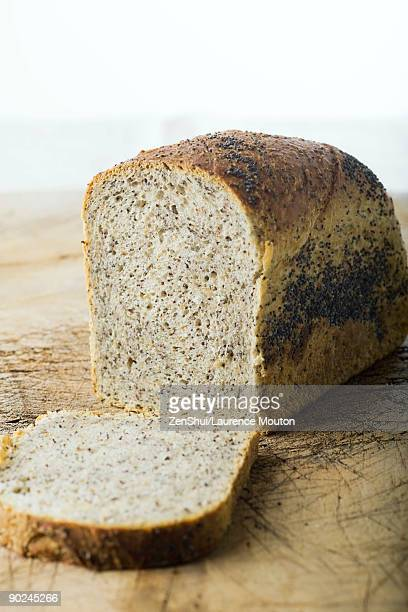 Loaf of bread, one slice resting on cutting board