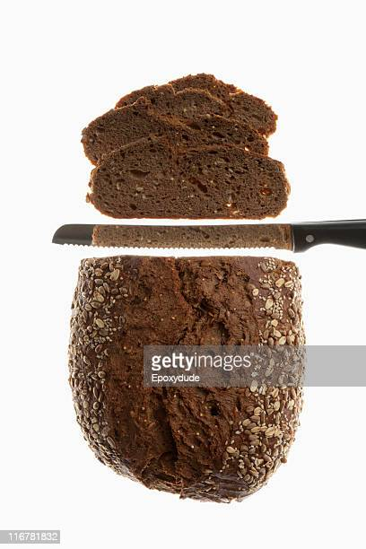 A loaf of bread, sliced with a bread knife