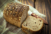 Sliced Homemade whole grain bread on plate. Freshly baked, sunflower,sesame and pumpkin seeds are spread all over