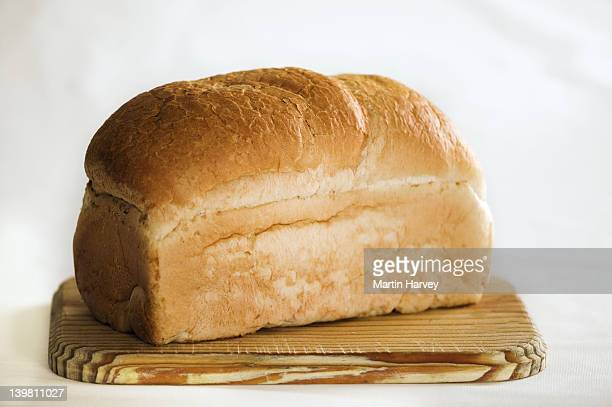 Loaf of white bread on cutting board.Against white background.