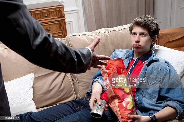 A loafing teenager being yelled at by his father