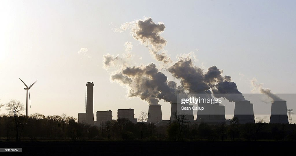 A loan wind turbine spins as exhaust plumes from cooling towers at the Jaenschwalde lignite coalfired power station which is owned by Vatenfall April...