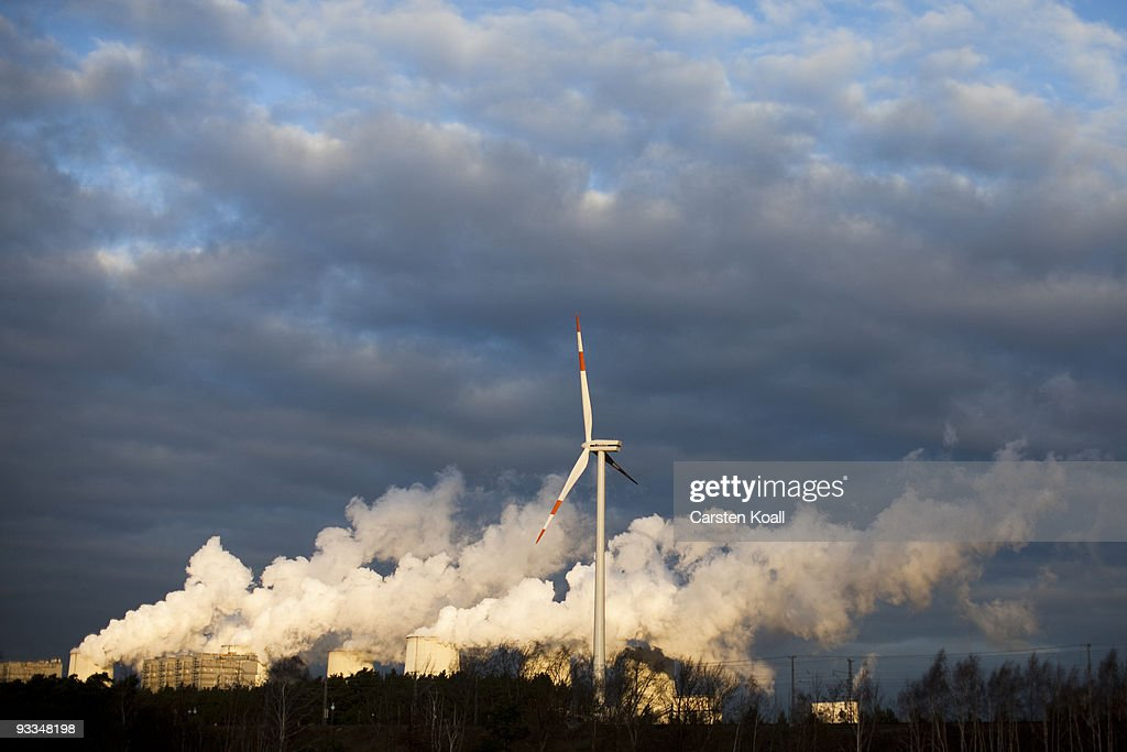 A loan wind turbine spins as exhaust plumes from cooling towers at the Jaenschwalde lignite coal-fired power station, which is owned by Vatenfall, on November 24, 2009 in Janschwalde, Germany. The CO2 emission will be one top of the agenda and will be discussed at the summit in December in Copenhagen.